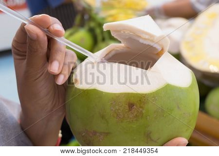 Woman hand holding fresh fragrant coconuts on flea market background Most pure drink of all the juices