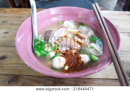 Close up Pork Hot Noodles with Dumpling Thai Style in Pink Ceramic Bowl on Wood Table