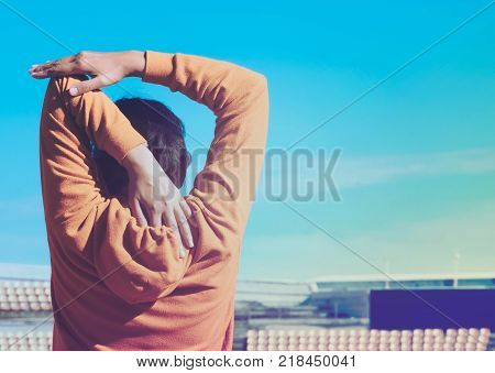 Southeast asian sport girl in orange Jacket warm up her body befor running at sport complex with beautiful sky