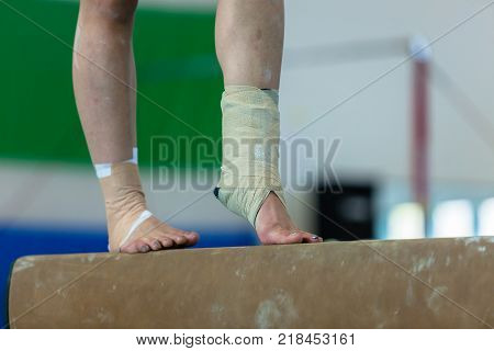 Gymnastics teenager girl closeup legs feet ankles bound with tape strapping from injuries on balance beam routine.