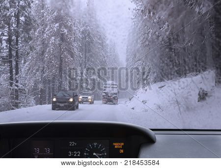 View from the car window on winter road with cars and truck in snowy forest. Heavy snow blizzard.