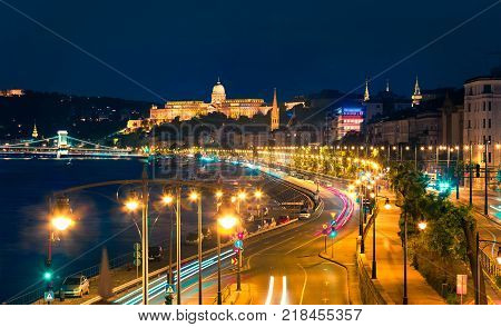 Evening view of Buda Castle with city lights and ship on the Danube river. Colorful cityscape in Budapest Hungary Europe. Artistic style post processed photo.