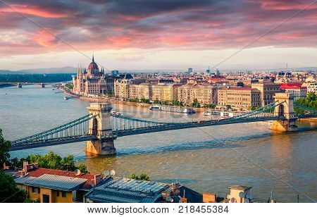 Colorful cityscape of Hungarian parliament building with famous Chain Bridge on the Danube river. Dramatic spring sunset in Budapest Hungary Europe. Artistic style post processed photo.