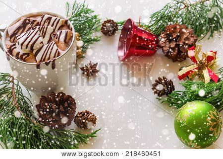 Hot chocolate in white cup topping with marshmallow andchoco late sauce. Delicious hot cocoa or chocolate on wood table with copy space in Christmas theme and snowfall bokeh background. Concept to present Christmas drink. Hot chocolate ready to served.