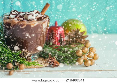 Hot chocolate in glass cup topping with marshmallow and chocolate sauce. Hot cacao or chocolate on wood table with copy space in Christmas theme and snowfall on blue background. Concept to present Christmas drink. Delicious hot chocolate ready to served.