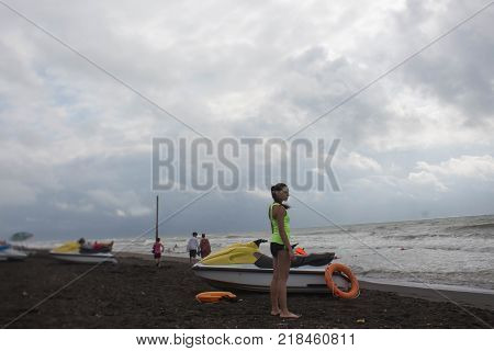 Girl lifeguard on duty keeping on the beach. Water scooter Lifeguard rescue equipment orange preserver tool on beach. Safety rescue vacation