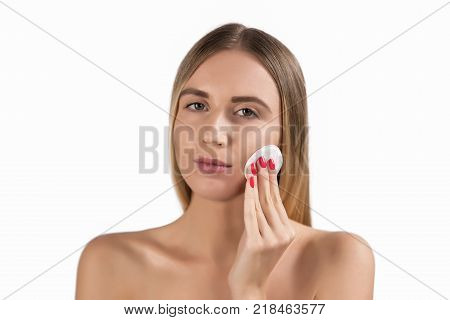beauty people and skincare concept - young woman cleaning face with exfoliating sponge