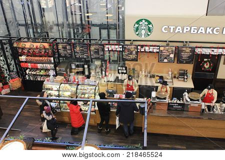 ST. PETERSBURG, RUSSIA - DECEMBER 9, 2017: Starbucks Coffee Shop Interior with Baristas Making Coffee. Shop Front with Counter Top View. Famous International Coffee Shop Company, Operating Worldwide.