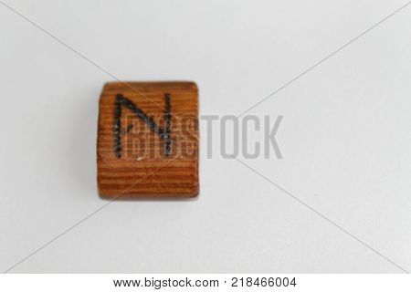 "Wooden rune which means ""hail"" (the precipitation) lie on a table on a white background"