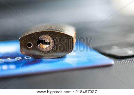 Padlock on credit card, laptop, credit card security conceptual image.