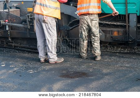 Road construction workers, asphalting machinery, road rehabilitation project in progres.