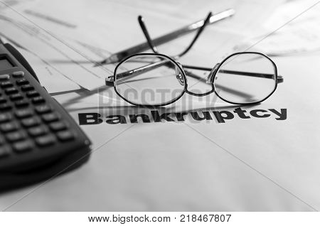 Bankruptcy notification,calculator, eyeglass, pencil and unpaid bills in the background in black and white.