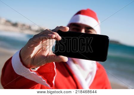 closeup of santa claus taking a self-portrait of himself with his smartphone on the beach