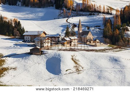 The small village of St. Magdalena or Santa Maddalena with its church covered in snow and with the Odle or Geisler Dolomites mountains in the Val di Funes Valley South Tyrol Italy in winter.