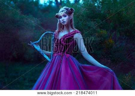 Beautiful young elf woman dressed in long purple dress walking through the summer forest