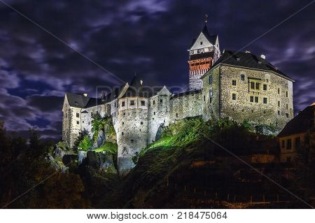 Loket Castle is a 12th-century Gothic style castle located about 12 km from Karlovy Vary on a massive rock in the town of Loket Czech Republic. Evening