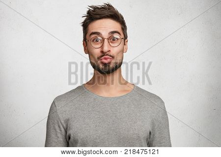 Portrait of bearded young male wears round spectacles and rounds lips has trendy hairdo and wears casual sweater isolated over white background. Stylish unshaven man in studio makes grimace poster