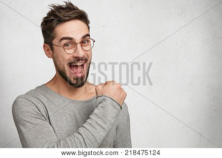 Portrait Of Bearded Young Male Wears Round Spectacles And Rounds Lips, Has Trendy Hairdo And Wears C