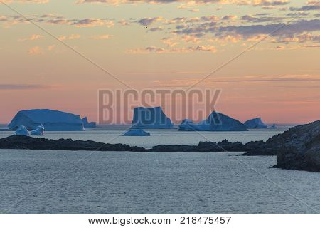 group of icebergs at sunset; Fogo Island, Newfoundland, Canada