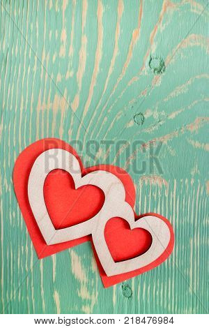 Two carved wooden hearts are lying on red paper hearts on light green painted textured wooden table with stripes and squiggly stains and copy space. Top view.