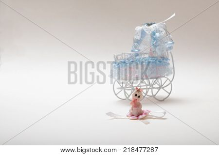 Sweet baby  doll  with brown curly hair in diaper with a pacifier  in mouth. sitting in front of a doll house baby carriage . high quality image with copy space