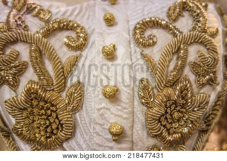 Vintage gold embroidery with floral pattern on an old white dress with gold buttons closeup.