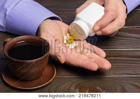 Male hand holds vitamin complex and dietary supplement capsules of omega 3 glucosamine calcium pills cup of black coffee on dark wooden table.