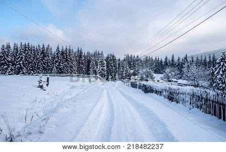 winter countryside with snow covered road isolated house with fence forest and blue sky with clouds above Moravka village in Moravskoslezske Beskydy mountains in Czech republic