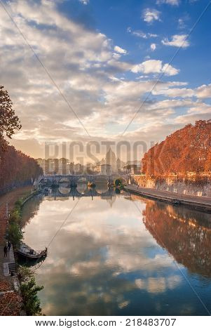 Autumn leaves along River Tiber in Rome with Saint Peter dome Holy Angel Bridge and old sunken ship at sunset
