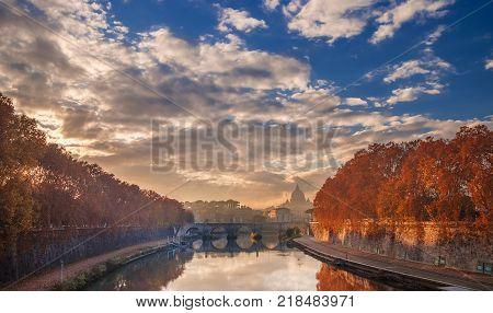 Autumn leaves along River Tiber in Rome with Saint Peter dome and Holy Angel Bridge at sunset