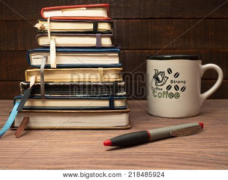 A stack of multicolored notebooks neatly laid on a wooden table and a cup of strong coffee
