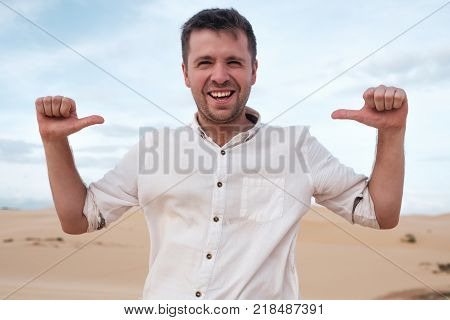 Self-satisfied and proud caucasian young man looks forward showing with index fingers on himself on desert. He is not afraid of being lost or alone