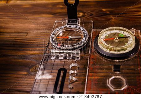 Two touristic magnetic compasses on a rustic wooden table