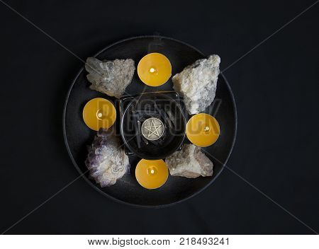 Circle of candles and natural stones, pentacle in center