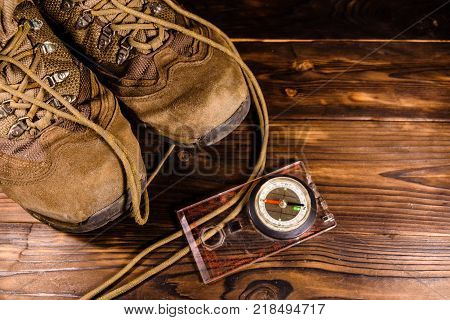 Touristic magnetic compass and boots on a rustic wooden table