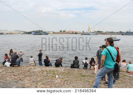 St. Petersburg, Russia - 28 July, People on the beach watching the parade, 28 July, 2017. Festive parade of warships on the Neva River in St. Petersburg.