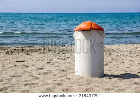 Trash can on the beach sunny day. Concept photo of a clean beach.