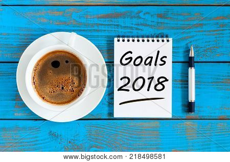 2018 goals on paper note book background and morning coffee cup on blue wood table, Targets, goal, dreams and New Year's promises for the next year.