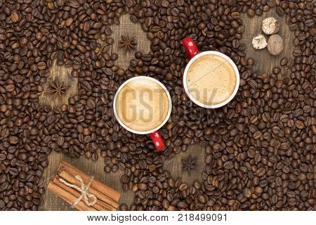 Two cups of coffee with a foam top view. Coffee beans badon cinnamon on a wooden surface with place for text. Love of a coffee drink. Morning invigorating coffee for two with copy space.