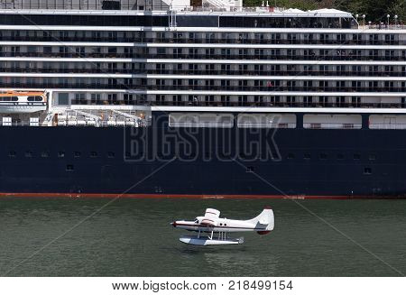 The small airplane landing on a water next to the cruise liner in Juneau town (Alaska).