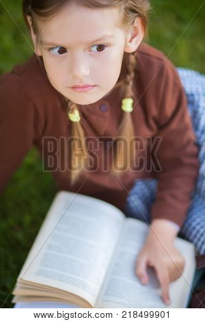 Adorable happy little preschooler girl with pigtails ready back to school reading textbooks outdoors school books manuals. Wearing school uniform. Warm september fall day. Smart clever intellegent little girl. poster