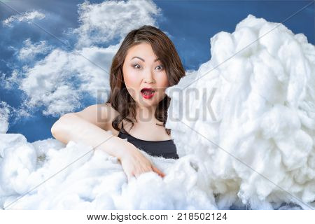 asian woman with open mouth and eyes wide open touching the clouds. weather concept.