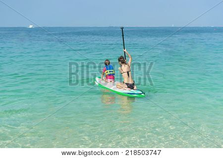 Mother and his adorable little daughter sitting on stand up board having fun during summer beach vacation
