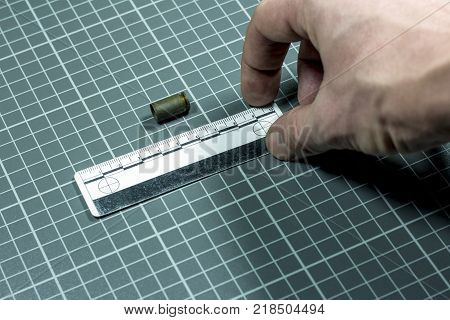 Close-up.The hand of the criminalist keeps a measuring ruler next to the cartridge bullet from the pistol on a checkered background.