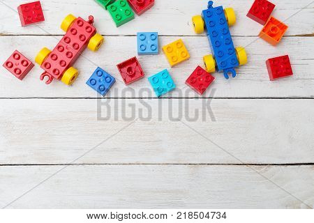 Lots of colorful plastic blocks constructor on wooden background. Copy space poster