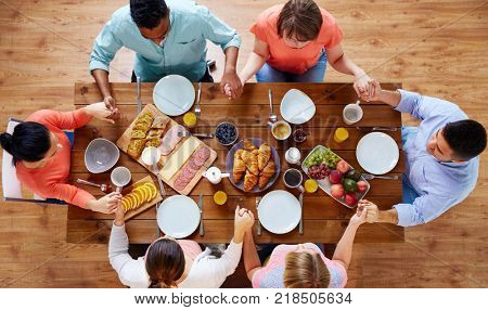 breakfast, family and religious concept - group of people with food sitting at table and praying before meal
