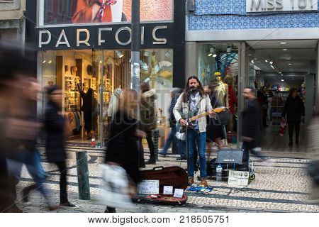 PORTO, PORTUGAL - MAR 4, 2017: Unknown street musician on one of the streets in old downtown. City of Porto was elected from 20 selected Best European Destination 2017 and won this prestigious title.