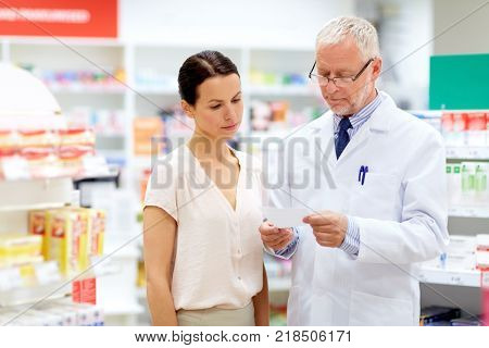 medicine, healthcare and people concept - senior apothecary reading prescription from female customer at pharmacy