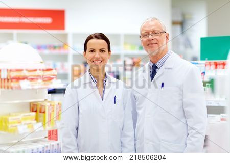 medicine, healthcare and technology concept - happy smiling apothecaries at pharmacy