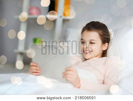 people, children and technology concept - happy smiling girl lying awake with tablet pc computer in bed at home over holidays lights